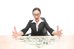 Young businesswoman looking at money scattered on table. Royalty Free Stock Photo