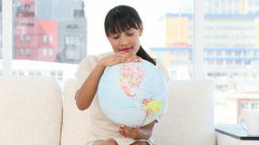Young businesswoman looking at a terrestrial globe Stock Photo