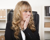 Young businesswoman looking worried. With her hand to her face in consternation as though realising she has made a mistake Royalty Free Stock Photos
