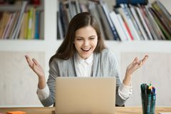 Young businesswoman looks at laptop screen with expression of ex Royalty Free Stock Images