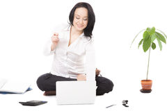 Young businesswoman in lotus pose typing on laptop on white back Stock Image