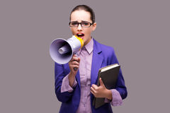 The young businesswoman with loudspeaker on gray background. Young businesswoman with loudspeaker on gray background Stock Image