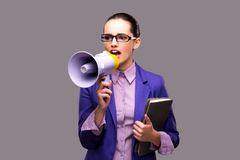 The young businesswoman with loudspeaker on gray background. Young businesswoman with loudspeaker on gray background Royalty Free Stock Images