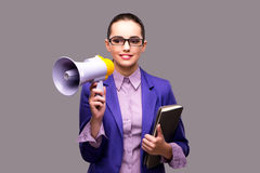 The young businesswoman with loudspeaker on gray background. Young businesswoman with loudspeaker on gray background Royalty Free Stock Photography