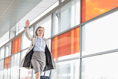 Young businesswoman with luggage running in railroad station Stock Image