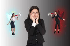 Young businesswoman making choice. Young troubled businesswoman making choice between good and bad on grey background Stock Images