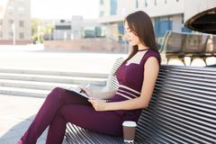 Young businesswoman making notes outdoors. Young businesswoman making notes in notebook, sitting on bench outdoors near modern office center, copy space Royalty Free Stock Photography