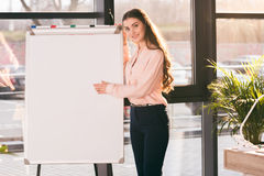 Young businesswoman making presentation in blank whiteboard and looking at camera Royalty Free Stock Photography