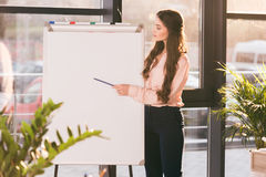 Young businesswoman making presentation and pointing at blank whiteboard Royalty Free Stock Photography