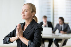 Young businesswoman meditating. Habits of successful woman, taking care of herself in personal and business life, staying present and cherishing all the good Stock Image