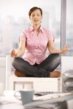 Young businesswoman meditating in office. Young businesswoman sitting in lotus posture on office cabinet, meditating Stock Photos