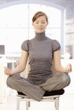 Young businesswoman meditating in office Royalty Free Stock Images