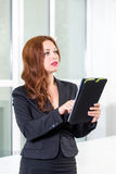 Young businesswoman in modern bright office holding the tablet with a list of tasks. Business concept of office work. Young businesswoman in modern bright royalty free stock image
