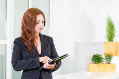 Young businesswoman in modern bright office holding the tablet with a list of tasks. Business concept of office work. Young businesswoman in modern bright stock photography