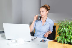 Young businesswoman in modern bright office with open notebook drinking hot morning coffee. Business concept. Stock Image
