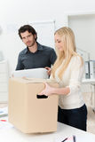 Young businesswoman moving into a new office. Carrying a large brown cardboard carton assisted by a male colleague Stock Images