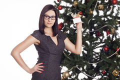 Young businesswoman near new year tree holding business card Stock Photos