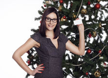 Young businesswoman near new year tree holding business card Royalty Free Stock Images