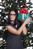 Young businesswoman near new year tree with present Stock Images
