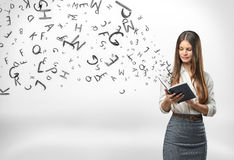 Young businesswoman with a notebook and letters flying out of it stock photos