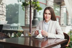 Young businesswoman outdoors drinking coffee. Smiling businesswoman drinking coffee, sitting at summer terrace cafe. Lifestyle portrait of young business woman Stock Photos