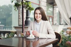 Young businesswoman outdoors drinking coffee. Smiling businesswoman drinking coffee, sitting at summer terrace cafe. Lifestyle portrait of young business woman Royalty Free Stock Photos