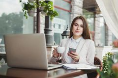 Young businesswoman outdoors using smartphone and drinking coffee. Thoughtful businesswoman working with laptop, drinking coffee and texting on smartphon Royalty Free Stock Photos