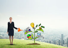 Young businesswoman outdoors watering drawn growth concept with can Stock Photo
