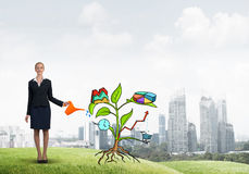 Young businesswoman outdoors watering drawn growth concept with can Stock Images
