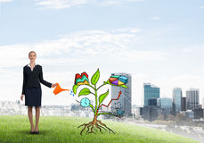 Young businesswoman outdoors watering drawn growth concept with can Stock Photography