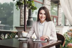 Young businesswoman outdoors working with laptop. Smiling businesswoman working with tablet, drinking coffee, sitting at summer terrace cafe. Lifestyle portrait Royalty Free Stock Photos