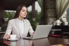 Young businesswoman outdoors working with laptop. Smiling businesswoman working with laptop sitting at summer terrace cafe. Lifestyle portrait of young business Stock Photography