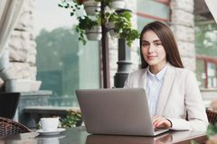 Young businesswoman outdoors working with laptop. Smiling businesswoman working with laptop sitting at summer terrace cafe. Lifestyle portrait of young business Royalty Free Stock Images