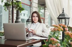 Young businesswoman outdoors working with laptop. Thoughtful businesswoman working with laptop, drinking coffee, sitting at summer terrace cafe. Lifestyle Stock Photo