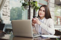 Young businesswoman outdoors working with laptop. Thoughtful businesswoman working with laptop, drinking coffee, sitting at summer terrace cafe. Lifestyle Stock Photos