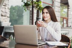 Young businesswoman outdoors working with laptop. Thoughtful businesswoman working with laptop, drinking coffee, sitting at summer terrace cafe. Lifestyle Stock Photography