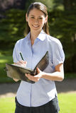 Young businesswoman with pen and folder outdoors, smiling, portrait Stock Photo