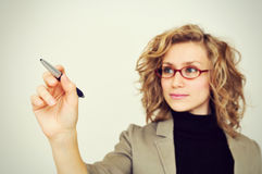 Young businesswoman with pen. In front of a virtual whiteboard. Focus on pencil stock photos