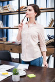 Young businesswoman with pen standing at desk and looking away Royalty Free Stock Photography