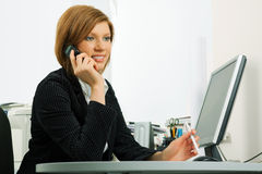Business woman calling on cell phone at office Stock Photo