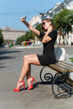 Young businesswoman with phone sitting on the Stock Photo