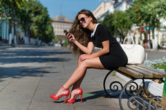 Young businesswoman with phone sitting on the Royalty Free Stock Photography