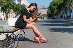 Young businesswoman with phone sitting on the Stock Photography