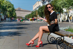 Young businesswoman with phone sitting on the Stock Photos