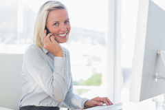 Young businesswoman on the phone smiling at camera. At her desk Royalty Free Stock Image