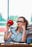 The young businesswoman with piggy bank in the office Stock Photography