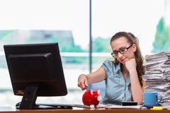 The young businesswoman with piggy bank in the office Stock Photo