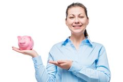 Young businesswoman with piggy bank on palm stock photo