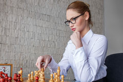 Young businesswoman playing chess in office Stock Photo