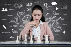 Young businesswoman playing chess royalty free stock image